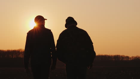 Two-Men-Farmer-Walking-Across-The-Field-At-Sunset-Chatting-Startup-In-Agribusiness