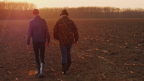 Middle-Aged-Farmer-With-His-Son-Walking-Across-The-Field-At-Sunset-Family-Farm-Concept