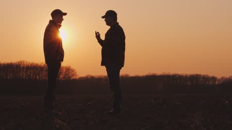 An-Elderly-And-Young-Farmer-Go-Together-Over-A-Plowed-Field-At-Sunset