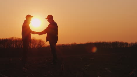 Two-Farmers-Shake-Hands-Standing-In-A-Field-At-Sunset