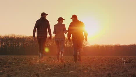 A-Team-Of-Young-Successful-Farmers-Walks-Across-The-Field-At-Sunset