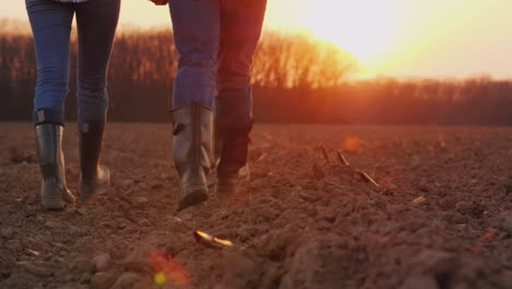 Legs-Of-Two-Farmers-In-Rubber-Boots-Walking-Along-A-Plowed-Field-At-Sunset-4k-Video