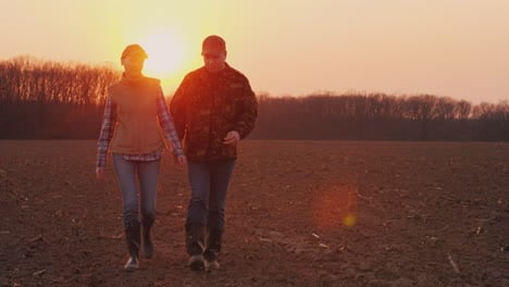 Two-Farmers-A-Man-And-A-Woman-Walking-Along-A-Plowed-Field-Talking