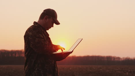 A-Middle-Aged-Farmer-Uses-A-Laptop-In-A-Field-At-Sunset-Plans-Sowing