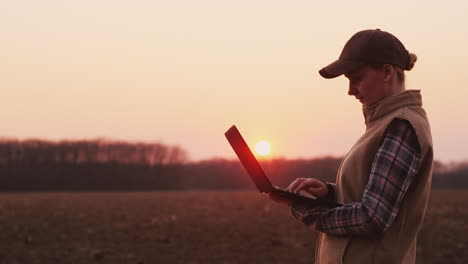 Young-Woman-Farmer-Works-With-A-Laptop-Near-Her-Field-At-Sunset
