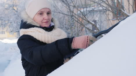 A-Woman-Removes-Snow-From-Her-Car