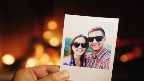 A-Hand-Holds-A-Burning-Photo-Of-A-Young-Couple-Then-Throws-It-Into-The-Fireplace