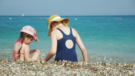 Two-Girls-Are-Sitting-On-A-Pebble-By-The-Sea-Looking-For-Beautiful-Pebbles-Holidays-With-Children-At