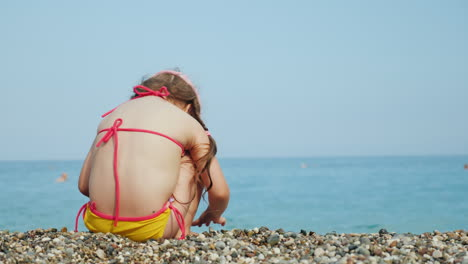 A-Lonely-Little-Girl-Collects-Beautiful-Pebbles-On-A-Sea-Beach-Sits-On-A-Pebble-Rear-View-4k-Video