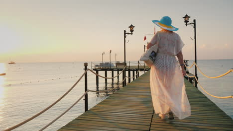 A-Woman-In-A-Pair-And-Hat-Walks-On-The-Pier-In-The-Early-Morning-Breathes-In-The-Fresh-Air-Steadicam
