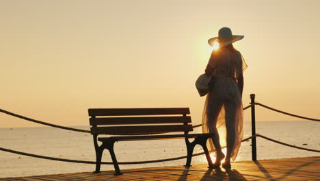 A-Lone-Silhouette-Of-A-Slender-Young-Girl-In-Developing-Clothes-And-A-Stylish-Hat-On-A-Sea-Pier-Near