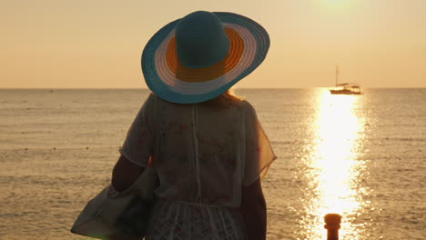 A-Young-Woman-In-Beach-Clothes-And-A-Wide-Brimmed-Hat-Is-Enjoying-The-Sunrise-On-The-Seashore-Going-