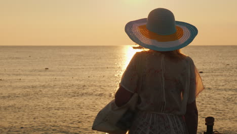 A-Slender-Tourist-Meets-The-Dawn-On-The-Sea-With-A-Bag-On-Her-Shoulder-And-A-Broad-Brimmed-Hat-On-He