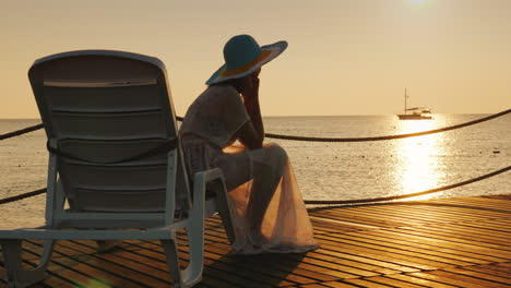 A-Woman-Looks-At-The-Sunrise-Over-The-Sea-Sits-On-A-Sunbed-In-The-Distance-A-Fishing-Boat-Is-Visible