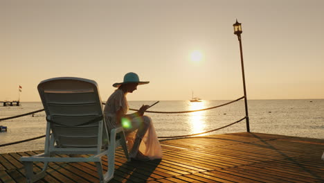 A-Woman-In-Summer-Clothes-Sits-On-A-Lounger-On-The-Pier-Uses-A-Tablet-A-Beautiful-Dawn-On-The-Sea-In