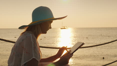 A-Woman-Uses-A-Tablet-On-Vacation-Sits-Against-The-Background-Of-The-Rising-Sun-Above-The-Sea-Always