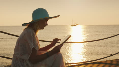 A-Tourist-With-A-Tablet-Sits-On-The-Pier-Picturesque-Sunrise-Over-The-Sea-In-The-Background-4k-Video