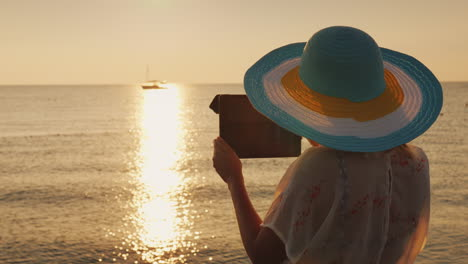 A-Woman-In-A-Hat-Is-Taking-Pictures-Of-A-Beautiful-Dawn-On-The-Sea-4k-Video