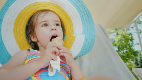 A-Little-Girl-In-A-Big-Hat-Enjoys-Eating-Ice-Cream-With-Pleasure-4k-Video