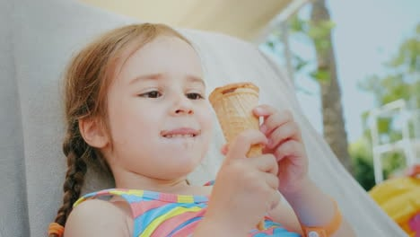 A-Happy-Little-Girl-Enjoys-Summer-Vacations-Lies-On-A-Couch-At-Sea-And-Eats-A-Delicious-Ice-Cream