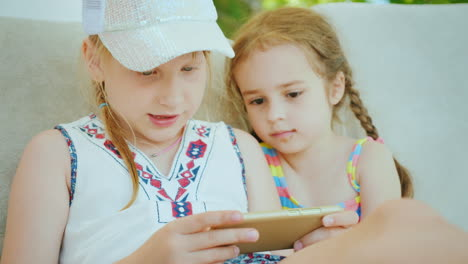 Two-Little-Girls-Are-Playing-On-The-Smartphone-They-Sit-Next-To-Each-Other-On-The-Beach-Chaise-Longu