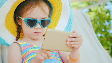 On-The-Beach-With-A-Smartphone-Little-Girl-Is-Playing-On-Smartphone-Is-Sitting-In-Big-Hat-In-Chaise-