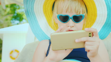 A-Cool-Girl-In-Sunglasses-In-The-Shape-Of-A-Heart-Uses-A-Smartphone-On-Vacation-4k-Video