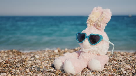 Pink-Hare-In-Sunglasses-Sits-On-Pebbles-Against-A-Blue-Sea