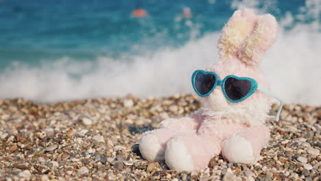 Plush-Rabbit-In-Sunglasses-Sunbathing-On-The-Beach-4k-Video