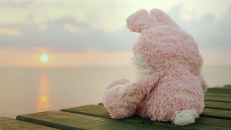 Pink-Toy-Hare-Sitting-On-The-Pier-Looking-At-The-Rising-Sun-4k-Video