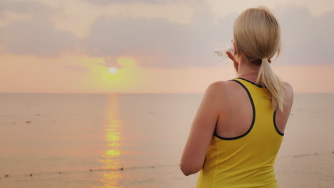 Fitness-Woman-Is-Drinking-Water-From-A-Bottle-It-Stands-In-A-Picturesque-Place-By-The-Sea-At-Dawn-Re