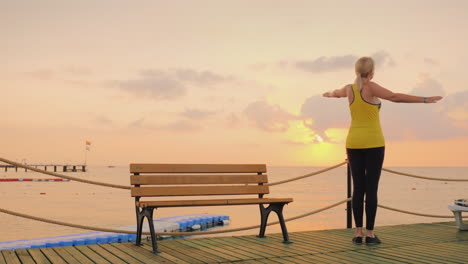 Active-Woman-Doing-Exercises-On-The-Pier-By-The-Sea-Where-The-Current-That-The-Sun-Rose-Start-A-New-