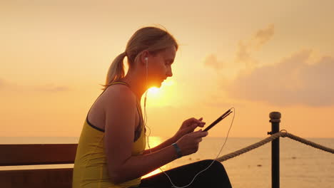 Fitness-Woman-Enjoys-A-Tablet-Sits-On-A-Bench-On-A-Pier-Against-The-Backdrop-Of-The-Rising-Sun-4k-Vi