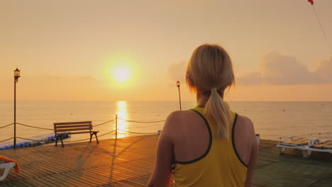 Middle-Aged-Woman-Warming-Up-On-The-Pier-On-The-Background-Of-A-Beautiful-Sunrise-By-The-Sea