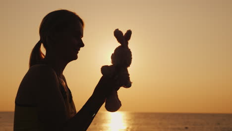 Silhouette-A-Woman-Is-Playing-With-A-Toy-Bunny-At-Dawn-Remember-Childhood-4k-Video
