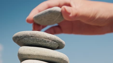 The-Hand-Puts-The-Stone-In-The-Tower-Balance-And-Balance-Concept-4k-Video