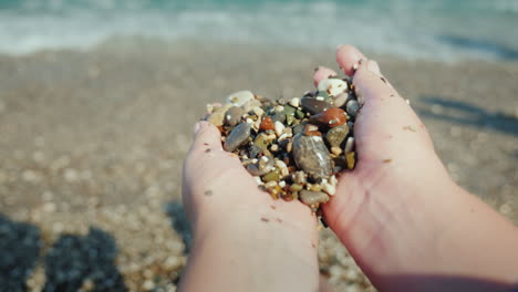 Female-Hands-Hold-A-Handful-Of-Wet-Pebbles-Rest-On-The-Sea-Meditation-Concept-4k-Video