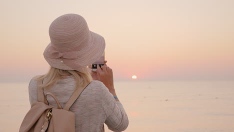 Young-Woman-Tourist-In-A-Pink-Hat-Makes-A-Photo-Of-The-Rising-Sun-On-The-Sea
