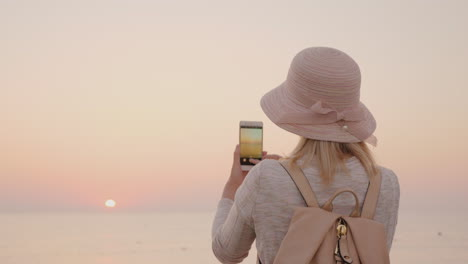 Young-Stylish-Girl-In-A-Hat-Takes-Pictures-Of-The-Sea-And-A-Pink-Sunrise-On-A-Smartphone
