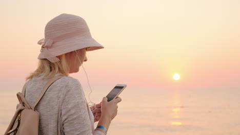 Not-A-Minute-Without-A-Phone-The-Girl-Is-Standing-On-The-Beach-With-A-Pink-Sky-And-Sky-Looking-At-Th