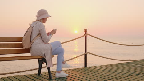 A-Stylish-Girl-In-A-Pink-Hat-Sits-On-A-Bench-On-A-Sea-Pier-And-Reads-A-Text-Message-On-The-Phone-The
