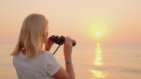 Young-Romantic-Woman-Looks-At-The-Sunrise-Over-The-Sea-Of-Pink-Color-Uses-Binoculars-4k-Video