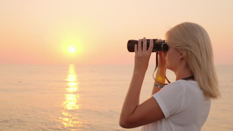 Attractive-Young-Woman-Looks-Through-Binoculars-At-Sunrise-Over-The-Sea-Romance-And-Adventure-4k-Vid