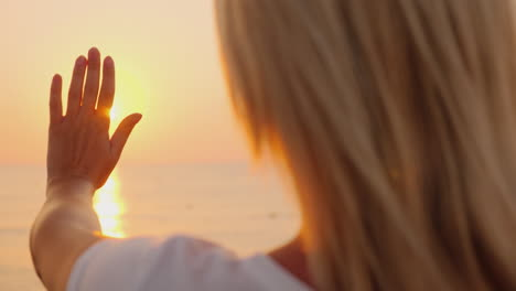 The-Woman-Extends-Her-Hand-To-The-Sun-Rising-Above-The-Sea-Enjoy-The-Warmth-And-Fly-Of-The-Concept