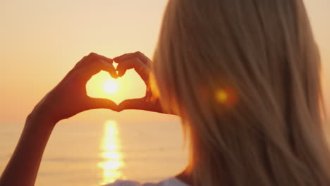 A-Woman-Holds-Her-Hands-In-The-Shape-Of-A-Heart-Looks-At-The-Ocean-Where-The-Sun-Rises-Love-And-Roma