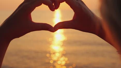 Female-Hands-Show-The-Shape-Of-The-Heart-Above-The-Sea-Where-The-Sun-Rises-Beautiful-Romantic-Scene