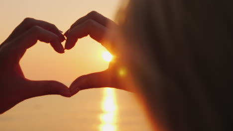 A-Woman-Hands-Shows-A-Heart-Symbol-Over-The-Sea-Where-The-Sun-Rises-Above-The-Rose-Water-Love-And-Ho