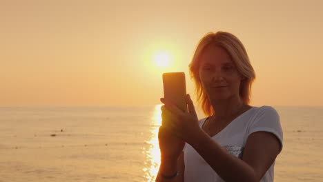 A-Young-Blonde-Woman-Is-Photographing-On-A-Smartphone-A-Pink-Dawn-By-The-Sea-View-From-The-Back