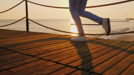 Morning-Jog-On-The-Pier-When-The-Sun-Rises-Over-The-Sea-In-The-Frame-Only-The-Legs-Are-Visible-Stead