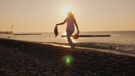 Carefree-Woman-With-A-Backpack-And-Hat-In-Her-Hands-Runs-Along-The-Seashore-At-Dawn-Summer-And-Vacat